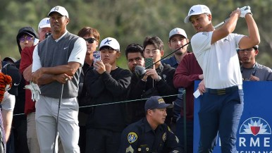 Tiger Woods watches drive by young Xander Schauffele of San Diego on Day 1 of Farmers Insurance Open.