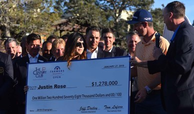Justin Rose accepts a symbolic check for more than $1.2 million after winning the 2019 Farmers Insurance Open in La Jolla.