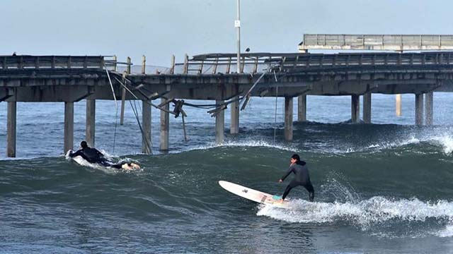 A surfer passes the damage to the railing of the Ocean Beach Pier during the king tide, peaking about 8 a.m. with an expected 7.3 tide.