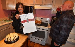 """Isabel Vasquez shows off cake box labeled """"To new beginnings"""" at Naranjo-McKercher party as her husband, retired UFCW Vice President Terry Hunt, takes a drink."""
