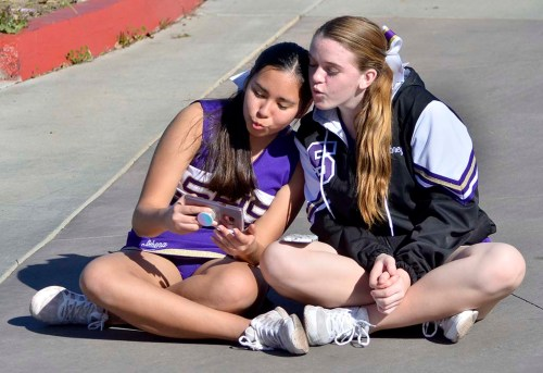 Santana High School cheerleaders check out something on a phone during the race ending after 7 1/2 hours.