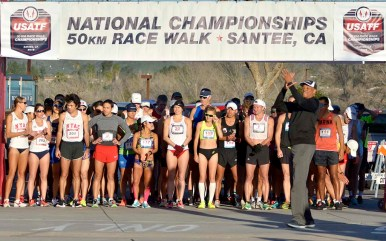 Former world-record triple jumper Willie Banks leads rhythmic clapping before start of race.