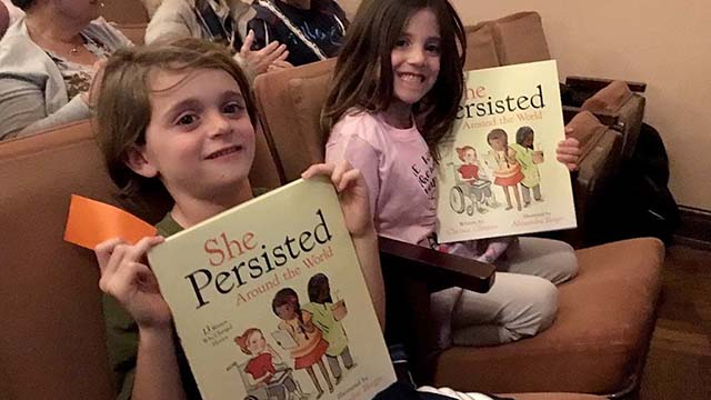 """Seated in the fifth row, Luke and Violet Walsh, 7 and 5, showed off their copies of """"She Persisted Around the World."""""""