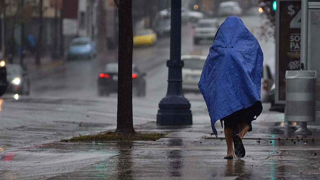 A homeless person wears a top over her to walk along a downtown street.