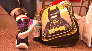 A mother with an ankle monitor waits with her child's backpack for the time to travel again.