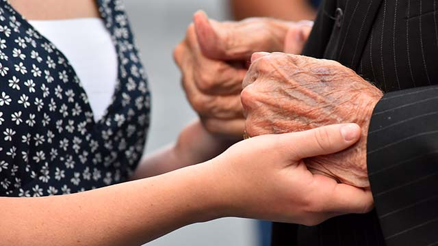 "Emerson Albright of San Diego, a new Navy enlistee, holds the hands of Battle of Midway veteran Ervin ""Judge"" Wendt during a passing of the torch anniversary ceremony."
