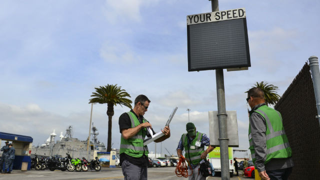 Safety specialists inspect one of Naval Base San Diego's radar speed signs