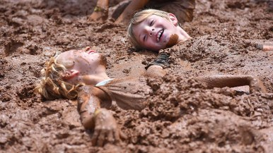 Quincy Yarbrough, 6 (left) and Luke Fassler, 6, both of Ocean Beach, share joy of being buried in mud at Mud Day activities in Mission Bay.