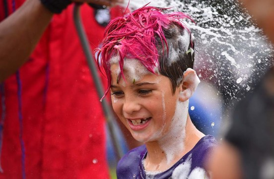 Jack Dede, 9, of North Park gets the soapy form washed out of his hair after participating in Mud Day activities.