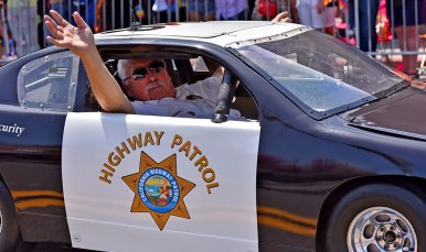 A mini Highway Patrol car is propelled down the parade route.