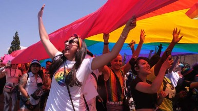 At the end of the San Diego Pride Parade, spectators gather under a large rainbow flag as it is moved along the parade route.