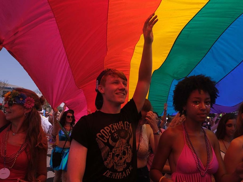 Parade goers walk under the long rainbow flag at the end of the San Diego Pride Parade.