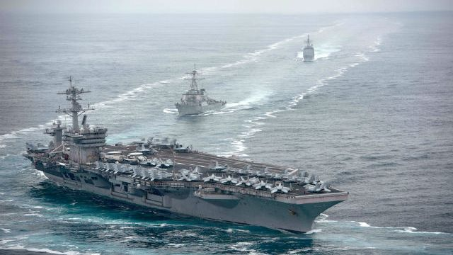 The aircraft carrier USS Theodore Roosevelt leads the USS Russell and USS Bunker Hill