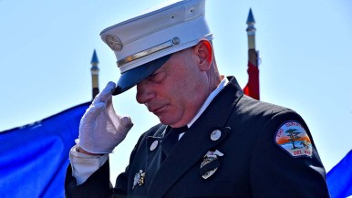 A captain with the Del Mar Fire Department salutes after reading names of the fallen, including a friend. Photo by Chris Stone