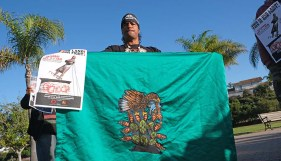 Jose Yanez of Jalisco, Mexico, displayed flag with Mexican coat of arms, recalling the legend of Tenochtitlan in the Aztec codices.