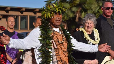 Kimokeo Kapalulehua, a Hawaiian elder, gives a blessing next to widow Mary Coakley Munk before the paddle out.