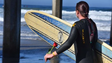 A participant readies for the paddle out at Scripps Pier in honor of ocean scientist Walter Munk who died in February.
