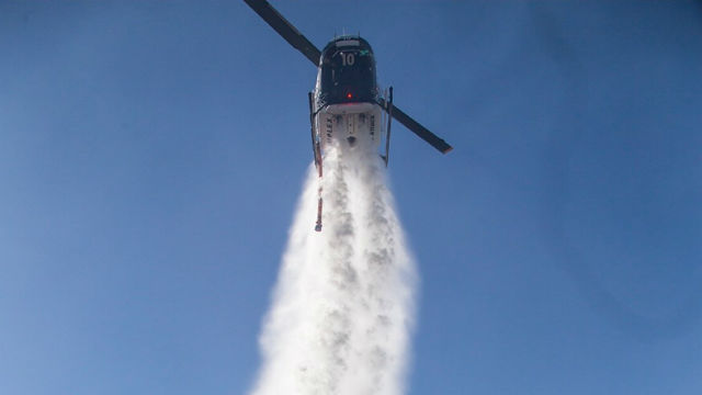 Helicopter drops water on Sawday Fire
