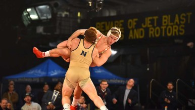 Navy's Tyler Dow lifts Wisconsin's Andrew Buckley in 184-pound match. Photo by Chris Stone