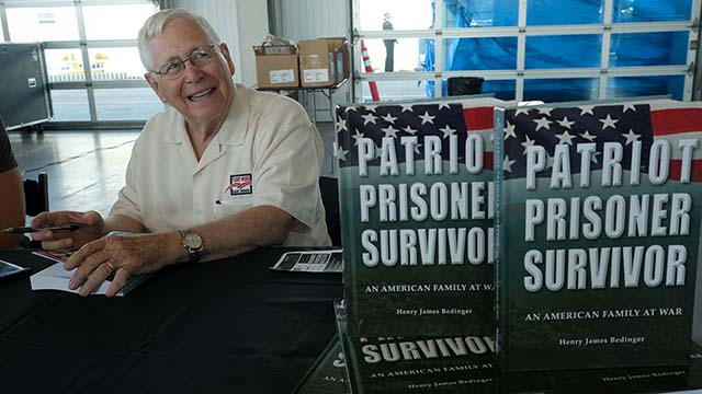 Retired Navy Cmdr. Henry James Bedinger visits with guests as he signs his book at Broadway Pier during Fleet Week.
