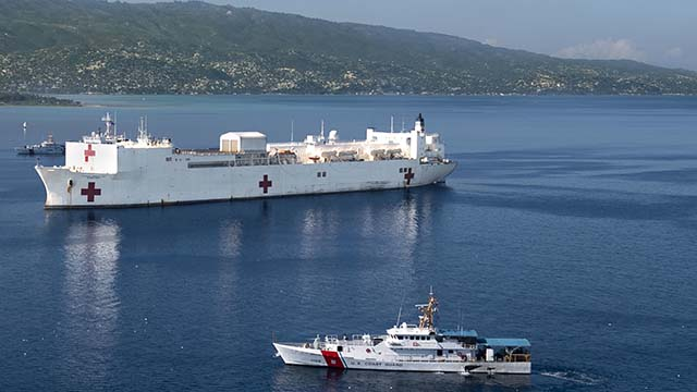 U.S. Coast Guard cutters pass the hospital ship USNS Comfort as it is anchored off the coast of Port-Au-Prince, Haiti in preparation for a six-day medical mission, Nov. 4, 2019.