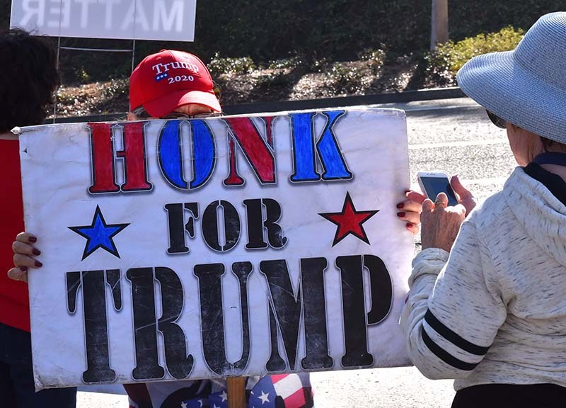 A few dozen supporters of President Trump line Avenida Del Oro in Oceanside to protest an appearance by Speaker Nancy Pelosi.