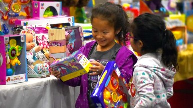 A girl shows a companion the toy she chose at Toys for Joy.