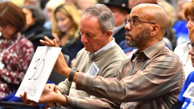 Kevin Haughton of Indivisible CBFD held countdown sign as Robert Vryheid (left) kept track of time for debate responses.