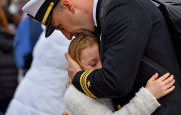 Lt. Cmdr. Luke Donahue comforts his daughter, Elaina,8, who had tears of joy when reuniting with her father.