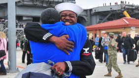 A USS Abraham Lincoln sailor is greeted by a family member.