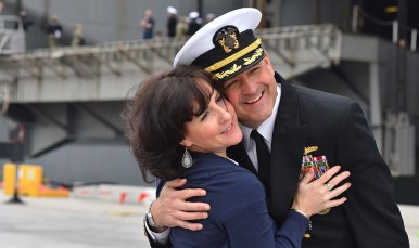 A Naval officer is greeted by his wife as the USS Abraham Lincoln arrives at its new home at Naval Air Station North Island on Coronado.