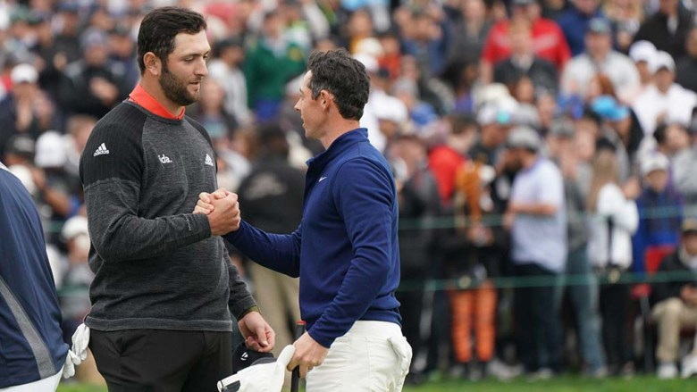 Jon Rahm (left) receives congratulations from fellow golfer Rory McIlroy.