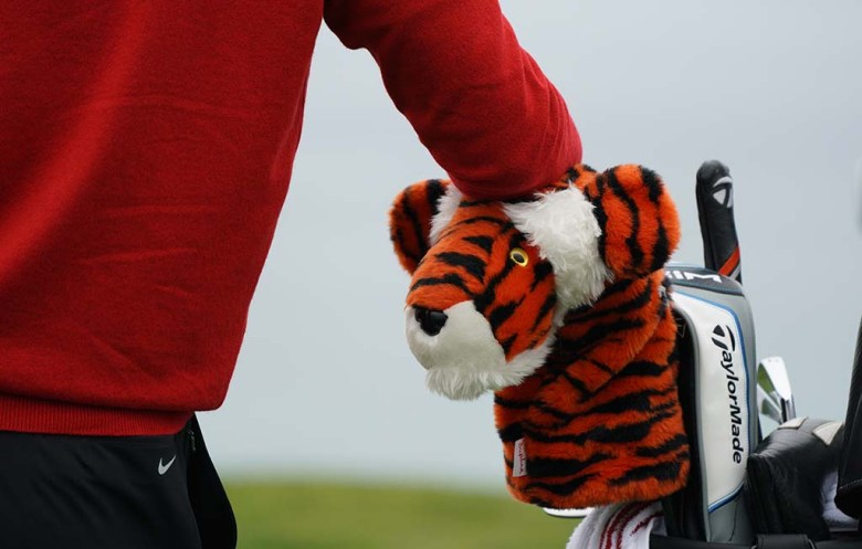 Tiger Woods leans on his clubs while waiting for play to end on the 3rd green of the south course.