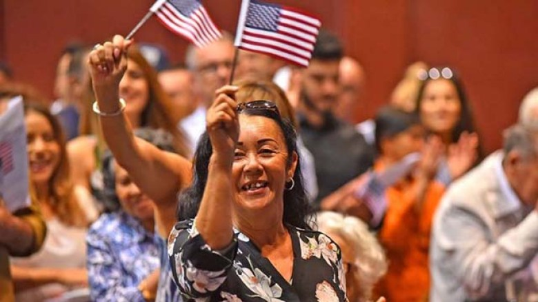 New citizens cheer after taking the oath of allegiance at Golden Hall in downtown San Diego in July 2018.