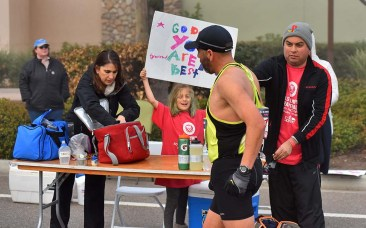 Adrian Zamudio, 44, of Santa Maria was cheered by his sign-holding daughter Ivy, 8, at drink station.