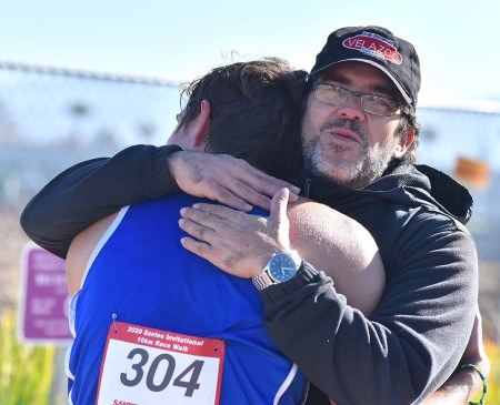 Oscar Gonzalez hugs his high school son, Andres, after he won the invitational 10K race at Santee.