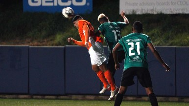 A San Diego Loyal player makes a header to stop the forward motion of the ball.