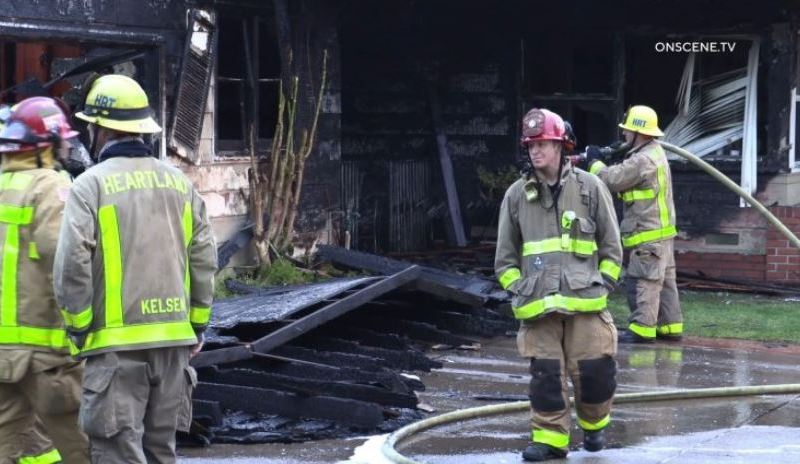 Firefighters outside gutted home