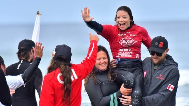 Victoria Feige of Canada is greeted by compatriots after she won the kneel division.