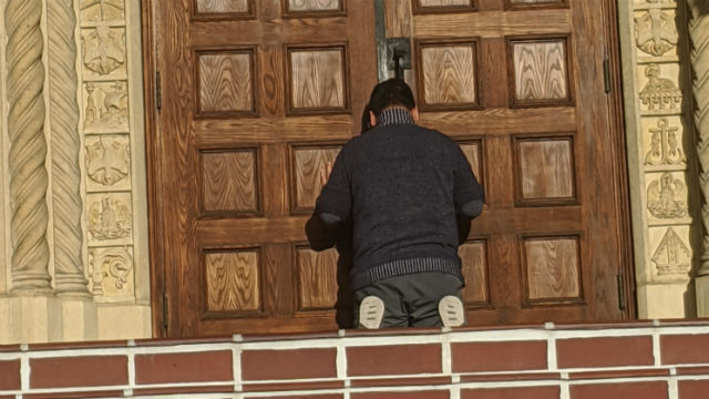 Worshiper at closed doors of St. Joseph Cathedral