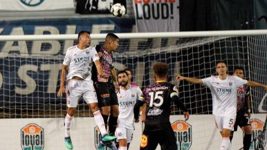 Carlos Alvarez of the San Diego Loyal player (left) jumps up to block an attempted goal.