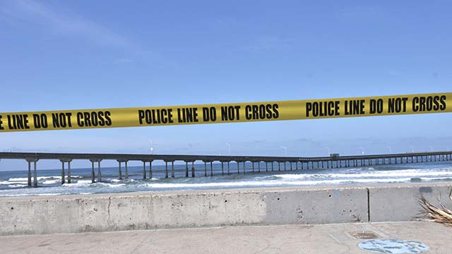 Police tape warns people not to go onto the beach at Ocean Beach Pier.