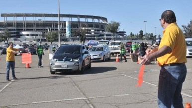 Todd Walters, president of UFCW Local 135, directs traffic at the food giveaway at SDCCD Stadium.