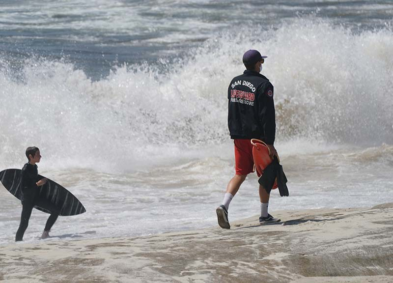 A lifeguard at Windansea patrols the beach as a surfer comes on shore.