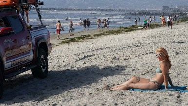 A lifeguard pulls up to tell a woman that sitting on the beach violates current beach rules.