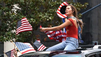 A flag-festooned car gives a lift to a woman hoisting a cowboy hat in old glory colors.