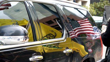 """American and """"Don't Tread on Me"""" flags reflect onto a SUV as it passes on Broadway in downtown San Diego."""