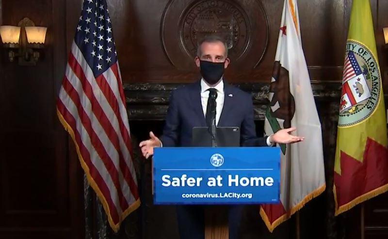 Eric Garcetti demonstrates a face mask