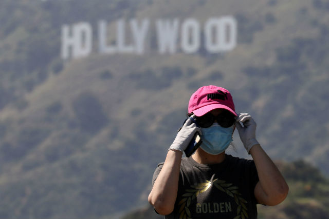 A hiker beneath the Hollywood sign wearing a face mask