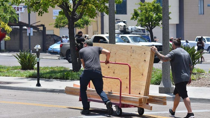 Volunteers paddle plywood on La Mesa street to help climb windows to protect the business in case looters return to La Mesa for the second night.